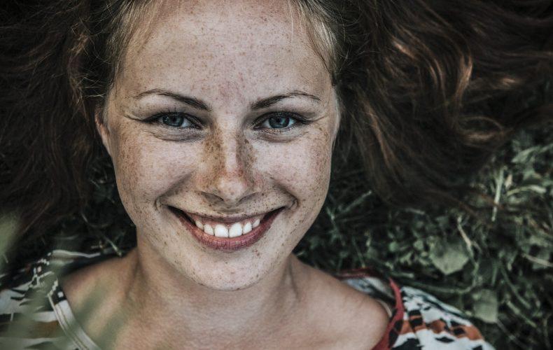 Kvinde der smiler med flotte tænder